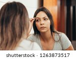 young woman plucking eyebrow... | Shutterstock . vector #1263873517