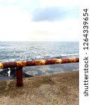 rusty railing against the sea | Shutterstock . vector #1264339654