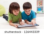 Boys playing labyrinth game on modern tablet computer - stock photo