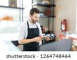 confident baker inserting... | Shutterstock . vector #1264748464