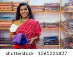 Small photo of business lady in red traditional sari and jewelery clothes shop owner cashmere yak wool shawls.female seller in goa india arambol sale shop.designer seamstress tailor girl choosing fabric