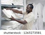 hotel worker african man lays a ...   Shutterstock . vector #1265273581