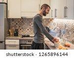 man in kitchen making juice... | Shutterstock . vector #1265896144