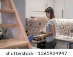 young woman in kitchen making... | Shutterstock . vector #1265924947