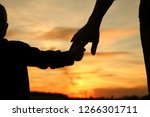 silhouette the parent holds the ... | Shutterstock . vector #1266301711