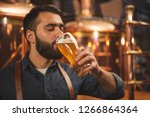 bearded male brewer sipping... | Shutterstock . vector #1266864364