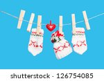Two gloves, hat and heart on clothesline with clothespins, blue background - stock photo