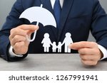 man holding cutout paper family ... | Shutterstock . vector #1267991941