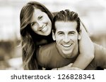 Portrait of smiling young man piggybacking his pretty girlfriend in the park - stock photo