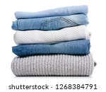 Stock photo stack of clothing jeans sweaters on a white background isolation 1268384791