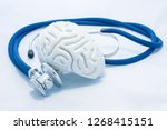 Small photo of Model of human brain with convolutions and blue stethoscope are on white uniform background. Concept photo health or pathological condition of human brain, diagnosing diseases of nervous system