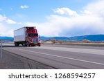 Big rig American bonnet powerful red semi truck with refrigerated semi trailer with refrigerator unit for cooling trailer inside space transporting commercial cargo on flat road in Utah - stock photo