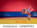 Two young men in blue and red wrestling tights are wrestlng and making a suplex wrestling on a yellow wrestling carpet in the gym. The concept of fair wrestling