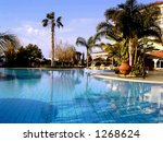 View on a swimming pool in exotic location (a holiday resort). - stock photo