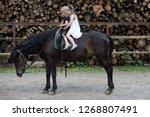 children sit in rider saddle on ... | Shutterstock . vector #1268807491