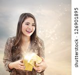 Girl Opening a Magical Golden Gift Box - stock photo
