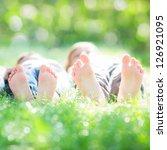 family lying on green grass in... | Shutterstock . vector #126921095