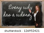 Small photo of Successful, beautiful and confident woman showing Every why has a wherefore on blackboard