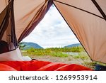 Campsite wilderness nature view of Yukon River, Yukon Territory, YT, Canada, from inside a tent with sleeping bag laid out