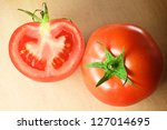 Photo of two fresh tomatoes on wooden cutting board - stock photo