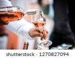 Stock photo pour white red wine and rose from the decanter and glass into the glass 1270827094
