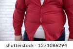 Small photo of Obese man wearing tight red shirt, oversize clothing problem, insecurities