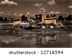 Earth Mover with reflections in water - sepia toned - stock photo