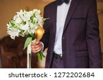 stylish groom holds white... | Shutterstock . vector #1272202684