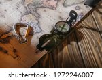 Small photo of close-up view of compass, spring hook and map on wooden table