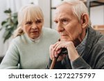 Small photo of selective focus of sad pensioner sitting near senior wife at home