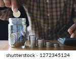 business man putting coin in... | Shutterstock . vector #1272345124