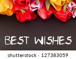 Bunch of tulips with blackboard: best wishes - stock photo
