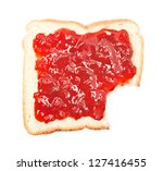 bite out of a slice of bread with strawberry jam on white background - stock photo