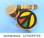 """Small photo of Close-up of three handmade Brazilian percussion instruments: small drum with drumstick, pandeiro (tambourine) and """"ganzá"""", a type of rattle. They are widely used to accompany the samba music."""
