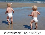 Twin Baby Boys Running On Beac...