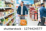 Small photo of At the Supermarket: Handsome Man Browses Through Shelf with Canned Goods, Looks at Tin Can. Walking with Shopping Cart Through Different Sections of the Store.