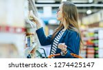 Small photo of At the Supermarket: Beautiful Young Woman Browses through the Canned Goods Section of the Store. She Has Shopping Basket Full of Healthy Food Items.