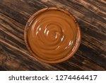 dulce de leche on wooden bowl | Shutterstock . vector #1274464417