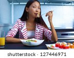 Young asian woman eating salad. - stock photo