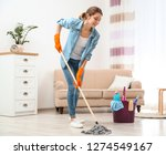 Young Woman Washing Floor With...