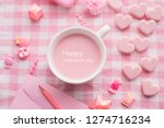 Valentine's day holiday celebration with cup of stawberries milk and Valentine decoration set on pink tablecloth texture background. top view.