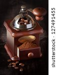 Old-fashioned handle coffee grinder with coffee beans on a dark wooden background. - stock photo