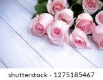 Stock photo beautiful and delicate bouquet of blooming roses in soft pink color on cream colored wood 1275185467