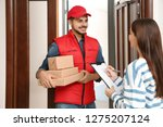 woman receiving parcels from... | Shutterstock . vector #1275207124