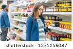 Small photo of At the Supermarket: Beautiful Young Woman Browses through the Canned Goods Section of the Store. She Checks Nutritional Value of Strawberry Jam. She Has Shopping Basket Full of Healthy Food Items.