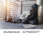 homeless man is sitting down on ... | Shutterstock . vector #1275602677