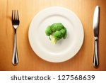 Photo of the fork and knife with white plate and broccoli on wood table - stock photo