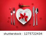 Stock photo plates in shape of heart holidays table setting with a gift box on red background 1275722434