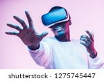 Small photo of African american man in vr glasses, playing video games with virtual reality headset, trying to touch something with hand