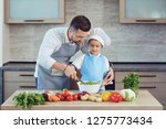 father and son are cooking in... | Shutterstock . vector #1275773434